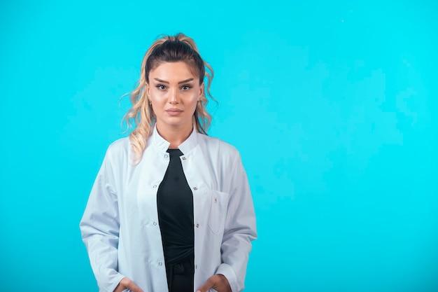 Médica de uniforme branco em postura profissional.