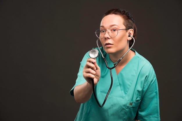 Médica de uniforme verde segurando um estetoscópio e ouvindo o paciente.