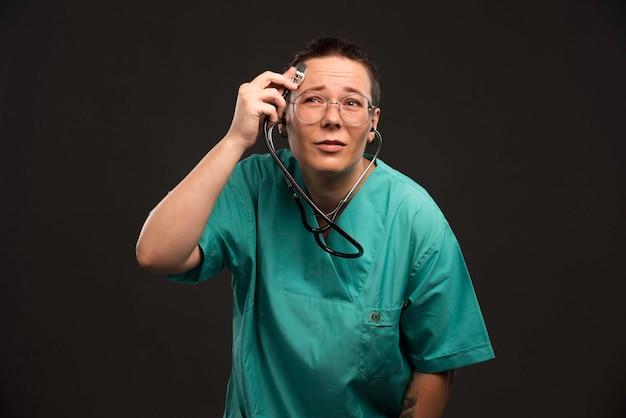 Médica de uniforme verde segurando um estetoscópio e verificando-o.