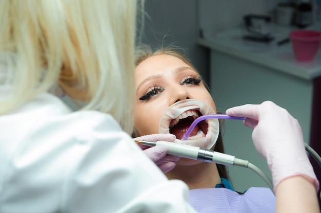 Médica de uniforme, verificando os dentes do paciente do sexo feminino na clínica odontológica.