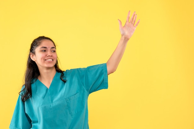 Médica de uniforme, vista frontal, saudando alguém