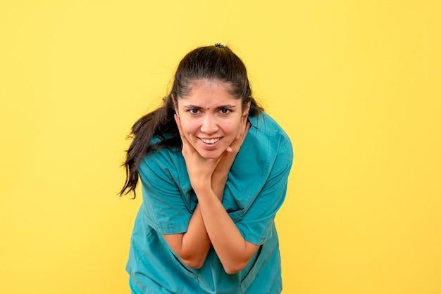 Médica de uniforme, vista frontal, segurando a garganta