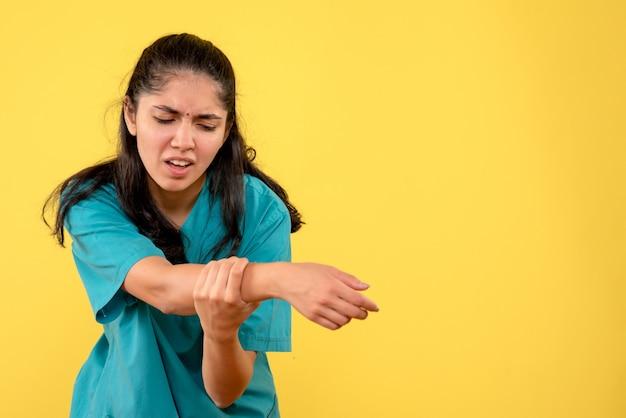 Médica de uniforme, vista frontal, segurando o braço dolorido