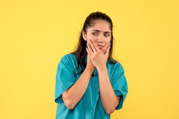 Médica de uniforme, vista frontal, segurando o rosto de pé
