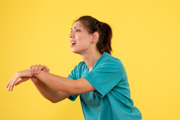 Médica de vista frontal com camisa médica e dor no braço em fundo amarelo