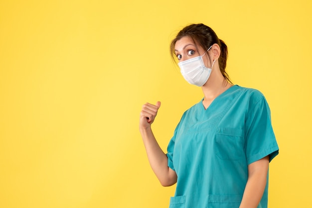 Médica de vista frontal com camisa médica e máscara em fundo amarelo