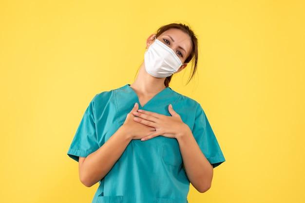 Médica de vista frontal com camisa médica e máscara estéril em fundo amarelo