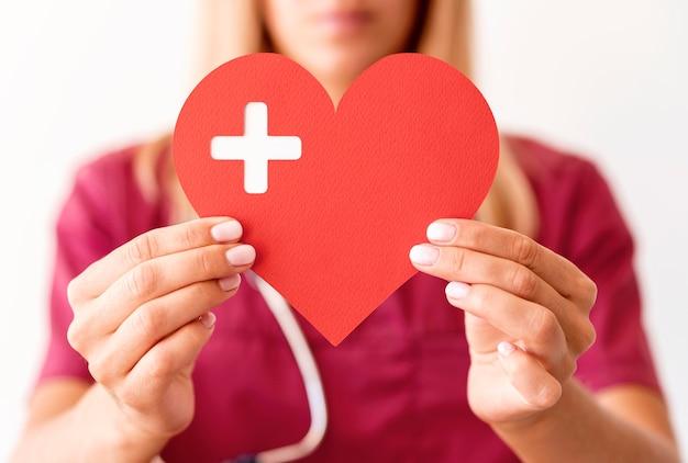 Médica desfocada segurando um coração de papel