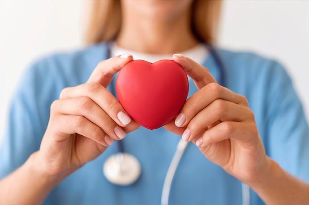 Médica desfocada segurando um formato de coração