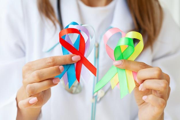 Médica detém fitas coloridas que simbolizam a consciência de várias doenças.