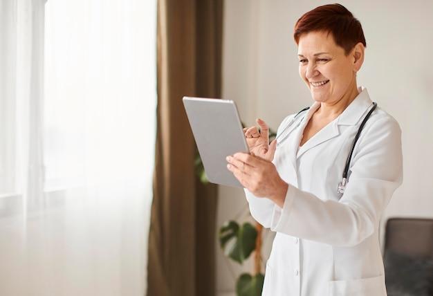 Médica do centro de recuperação cobiçoso, sorridente, idosa, com tablet e estetoscópio