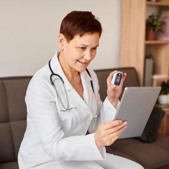 Médica do centro de recuperação cobiçoso, sorridente, idosa, com tablet e oxímetro