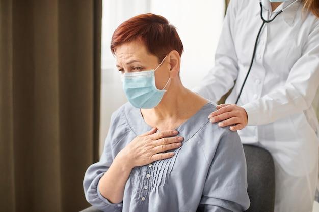 Médica do centro de recuperação da covid examinando paciente idoso com máscara médica