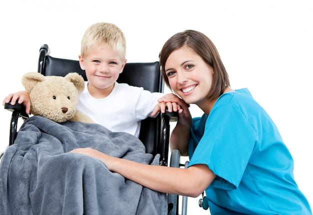 Médica do sexo feminino bonita que carrega um menino adorável com seu ursinho