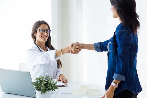 Médica do sexo feminino e seu paciente apertando as mãos na consulta.
