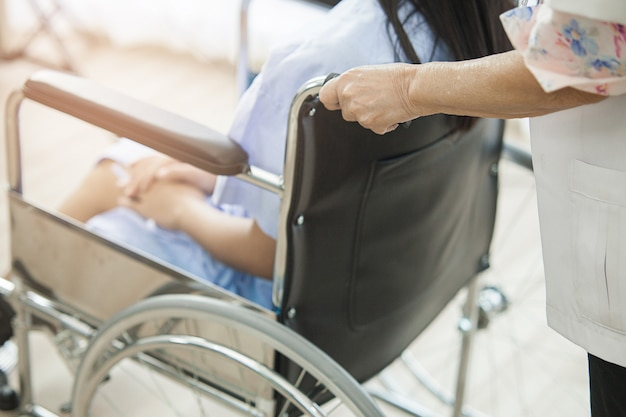 Médica é cadeira de rodas na qual um paciente jovem está sentado no hospital