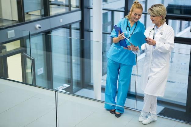 Médica e enfermeira discutindo sobre um relatório médico