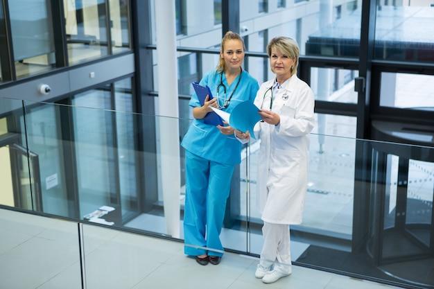Médica e enfermeira em pé no corredor