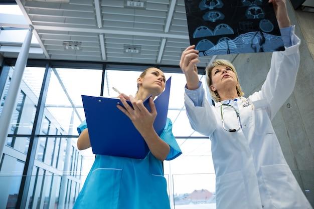 Médica e enfermeira examinando relatório de raio-x