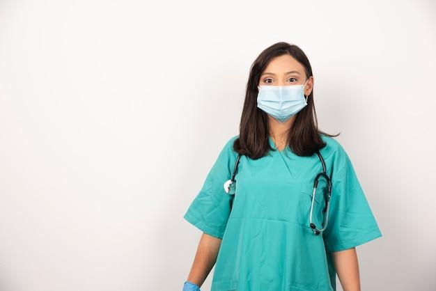 Médica em máscara e estetoscópio sobre fundo branco. foto de alta qualidade