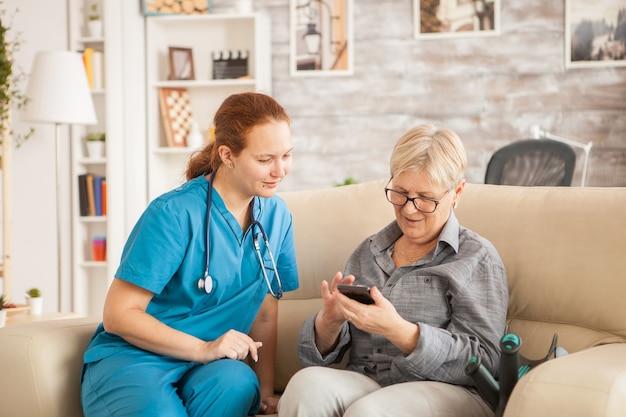 Médica em o lar de idosos, ajudando a velha a usar o telefone.