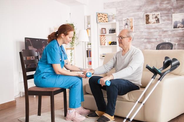 Médica em o lar de idosos, ajudando o velho com seu tratamento de reabilitação.
