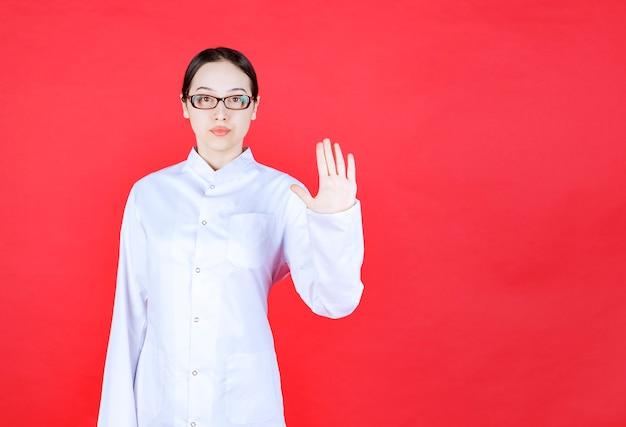 Médica em óculos de pé sobre fundo vermelho e parando algo com gests de mão.