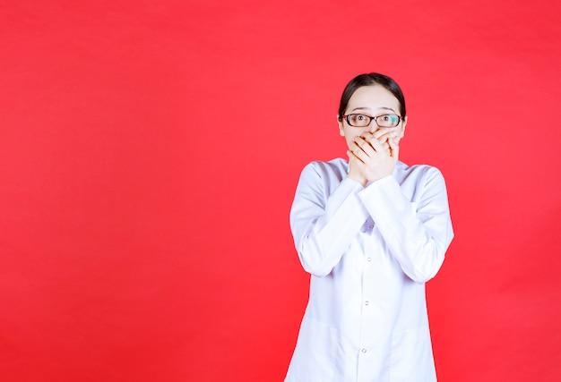 Médica em óculos de pé sobre fundo vermelho e parece assustada e apavorada.