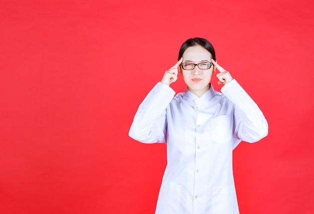 Médica em óculos de pé sobre fundo vermelho e pensando e brainstorming.