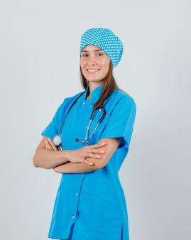 Médica em pé com os braços cruzados em uniforme azul e parece feliz. vista frontal.