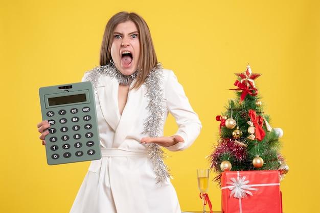 Médica em pé de frente e com raiva segurando a calculadora em um fundo amarelo com uma árvore de natal e caixas de presente