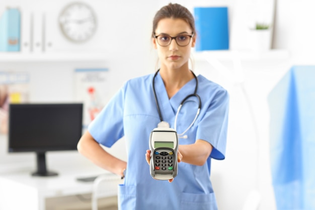 Médica em pé em seu consultório com terminal de pagamento