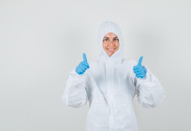 Médica em traje de proteção, luvas mostrando dois polegares para cima e parecendo feliz