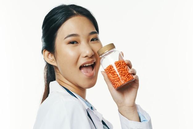 Médica em tratamento farmacêutico de comprimidos de jaleco branco