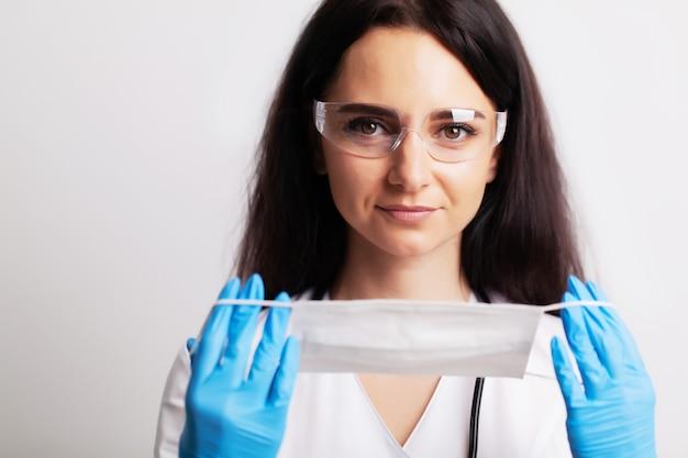 Médica em um jaleco branco coloca uma máscara cirúrgica no rosto
