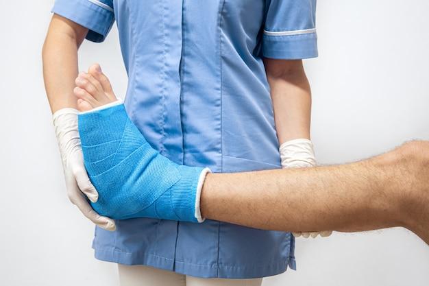 Médica em um vestido azul médico, verificando a perna quebrada em um paciente do sexo masculino.