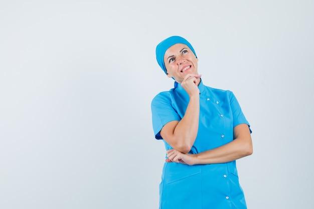 Médica em uniforme azul, apoiando o queixo na mão e olhando hesitante, vista frontal.