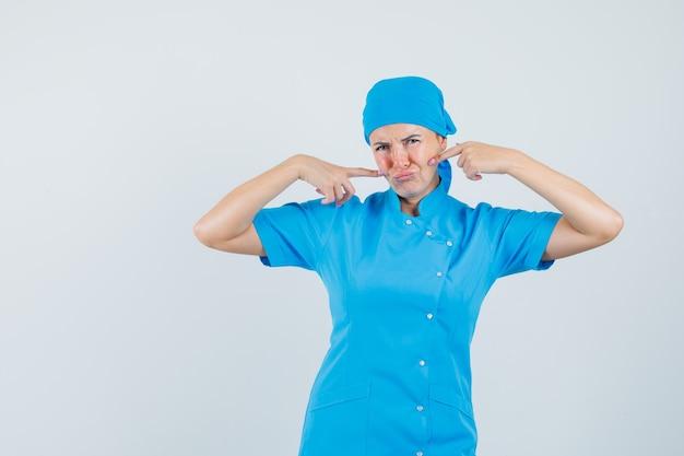 Médica em uniforme azul, apontando os dedos para as bochechas e olhando triste, vista frontal.