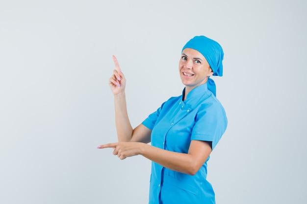 Médica em uniforme azul, apontando os dedos para cima e para baixo e olhando hesitante, vista frontal.