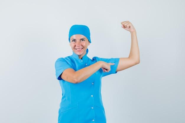Médica em uniforme azul, apontando os músculos do braço e olhando confiante, vista frontal.