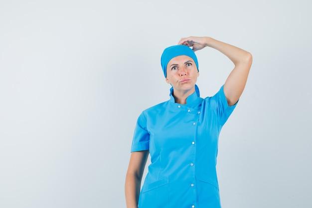 Médica em uniforme azul, coçando a cabeça e olhando pensativa, vista frontal.