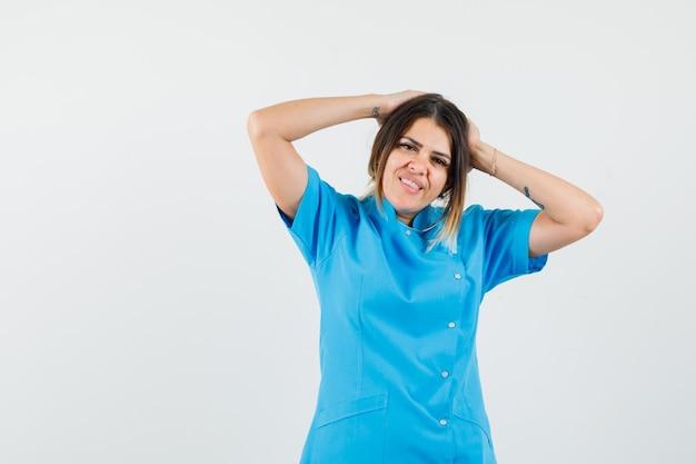 Médica em uniforme azul de mãos dadas atrás da cabeça e parecendo alegre