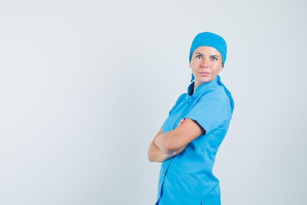 Médica em uniforme azul em pé com os braços cruzados e parecendo confiante.