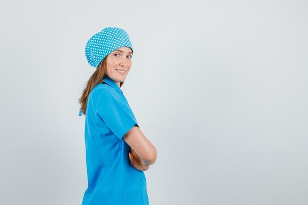 Médica em uniforme azul em pé com os braços cruzados e parecendo feliz.
