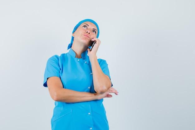 Médica em uniforme azul, falando no celular e olhando pensativa, vista frontal.