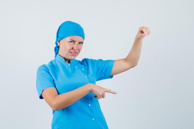 Médica em uniforme azul, fingindo segurar algo, apontando para baixo e parecendo descontente, vista frontal.