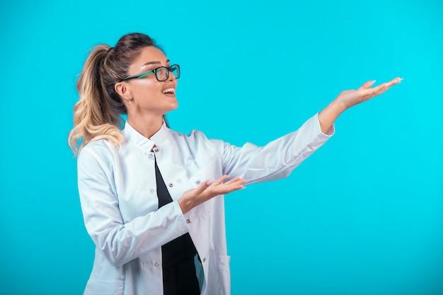 Médica em uniforme branco e óculos.