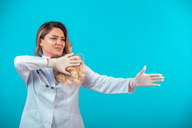 Médica em uniforme branco, mostrando a direção.