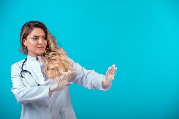 Médica em uniforme branco, parando algo à frente.