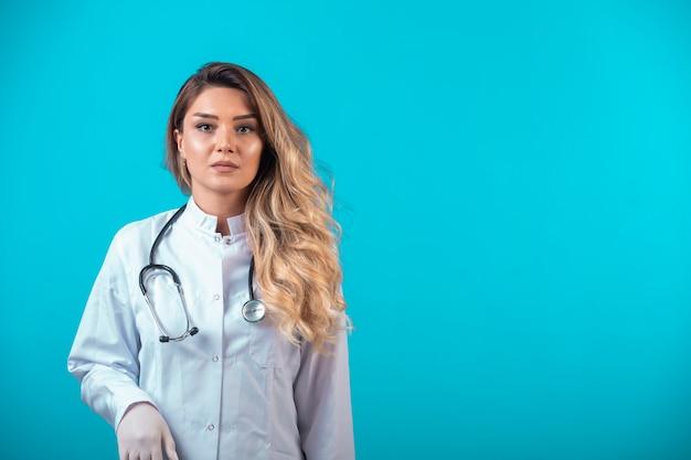 Médica em uniforme branco.